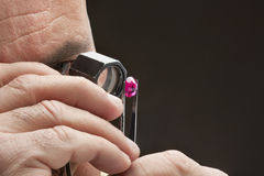 Cropped image of jeweler examining jewel over black background Stock Images