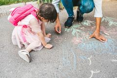 Cropped image of little girl and dad drawing with colorful chalks on the sidewalk. Handsome male play together with his cute kid. Preschooler outdoor in the royalty free stock photos
