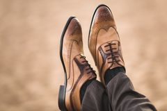 Cropped image of male brown shoes on men. Sitting on a beach Stock Image