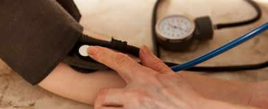 Cropped image of male doctor checking blood pressure of patient at table.  Stock Photos