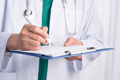 Cropped image of male doctor in medical office writing prescript. Ion Stock Photos