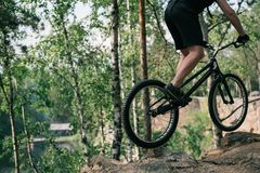 cropped image of male extreme cyclist jumping on mountain bike stock image