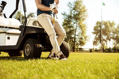 Cropped image of a male golfer leaning on a golf cart. Cropped image of a male golfer leaning on a cart and holding golf club outdoors Royalty Free Stock Images