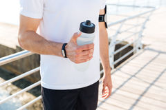 Cropped image of a male sportsman holding water bottle outdoors Stock Images