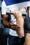 Cropped image of male trainer assisting fit woman. Cropped image of male trainer assisting fit women at gym Royalty Free Stock Image