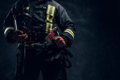 Cropped image of a male in uniform holding an oxygen mask and fire axe. Studio photo against a dark textured wall. Cropped image of a male in uniform holding an stock images
