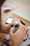 Cropped image of man adjusting camera lens at desk Stock Photography