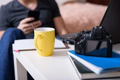 Cropped image of a man blogger sitting on the floor in front of a laptop, camera and notebooks, drinking from a yellow Cup and use royalty free stock photo