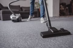 Cropped image of man cleaning carpet in living room. With vacuum cleaner stock photos