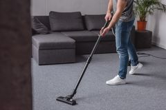 cropped image of man cleaning carpet with vacuum cleaner stock image