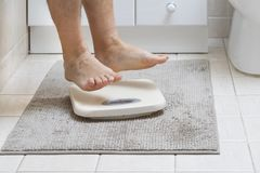 Cropped image of man feet jumping on weigh scale. On the bathroom floor royalty free stock photography