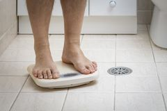 Cropped image of man feet standing on weigh scale. On the bathroom floor stock images