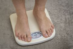 Cropped image of man feet standing on weigh scale royalty free stock photography