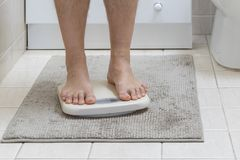 Cropped image of man feet standing on weigh scale royalty free stock photo
