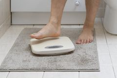 Cropped image of man feet stepping on weigh scale stock photos