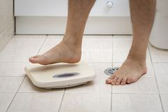Cropped image of man feet stepping on weigh scale royalty free stock photos