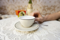 Cropped image of man having cup of coffee at table in cafe Stock Images