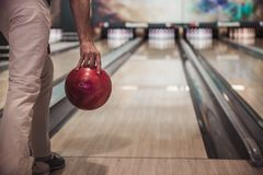 Man playing bowling. Cropped image of man holding a red bowling ball ready to throw it Royalty Free Stock Photography