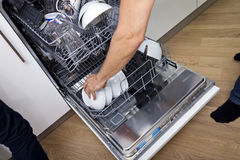 Cropped image of man loading dishwasher in kitchen Stock Photos