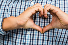 Cropped image of man making heart shape Stock Photos