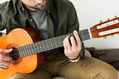 cropped image of man playing barre chord on acoustic guitar royalty free stock photography