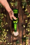 Cropped image of man pouring beer into glass at wooden table. With hop stock image