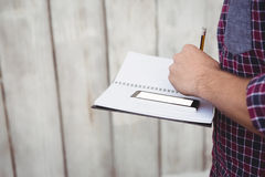 Cropped image of man with smartphone writing on book Stock Image