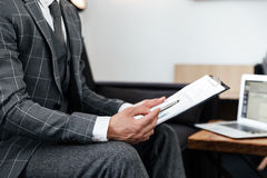 Cropped image of a man in suit analyzing documents. While sitting on a couch stock photo