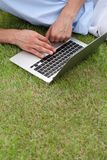 Cropped image of man using laptop on grass in park Royalty Free Stock Photography
