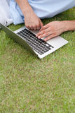 Cropped image of man using laptop on grass in park Stock Photography