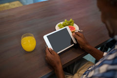 Cropped image of man using tablet. While sitting at table Royalty Free Stock Image