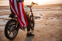 Cropped image of a man wearing american cape on motocycle. Cropped image of a brutal man wearing american flag cape sitting on his motocycle Royalty Free Stock Photo
