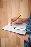 Cropped image of man writing on diary with pencil Stock Images