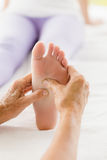 Cropped image of masseur giving foot massage to woman Royalty Free Stock Image