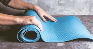 Cropped image of men hands rolling yoga mat royalty free stock photography