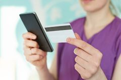 Cropped image of modern smart phone and plastic card in woman`s hands against blue blurred background. Young businesswoman checks stock photo
