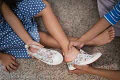 Cropped image of mother helping daughter to wear shoe royalty free stock image