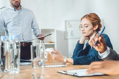 Cropped image of multicultural businesspeople sitting at meeting. In office royalty free stock photo