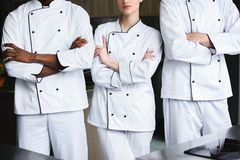 Cropped image of multicultural chefs standing with crossed arms. At restaurant kitchen stock photo