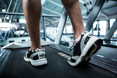 Cropped image of muscular man using treadmill Royalty Free Stock Images