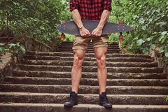 Cropped image of a muscular skater, standing on steps, holds the skateboard. Cropped image of a muscular skater, standing on steps, holds a skateboard Royalty Free Stock Photography
