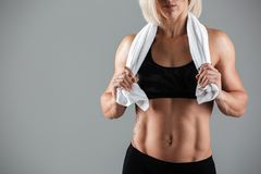 Cropped image of a muscular sportswoman holding a towel Royalty Free Stock Images