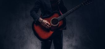 Cropped image of a musician in elegant clothes with a guitar in his hands playing and posing. Cropped image of a musician in elegant clothes with a guitar in royalty free stock photography
