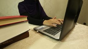 Young muslim woman working at office desk, documents and computer. Cropped image of a muslim woman working in her office through a computer, a young female stock video footage