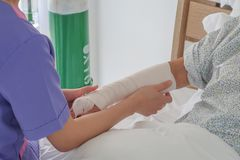Nures apply elastic bandage to broken arm of senior patient stock photo