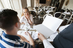 Cropped Image Of Waiter Showing Menu To Couple In Restaurant Stock Photo