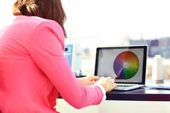 Cropped image of photo editor with color swatches working on laptop at desk royalty free stock photo