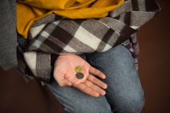 Poor man with coins. Cropped image of poor man holding coins on hand isolated on brown stock photography
