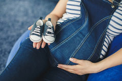 Cropped image of a pregnant woman little shoes stock image