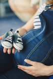 Cropped image of a pregnant woman little shoes Royalty Free Stock Photo